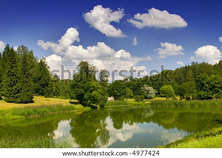 Landscape with blue sky, clouds, forest and lake