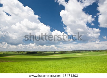 Landscape with blue sky white clouds and green grass.