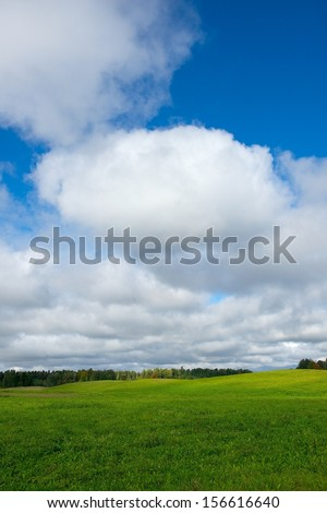 Landscape with cloudy sky background.Big cloudy sky background,Lithuania.Lithuanian nature with green grass field and big blue sky background, summer time. Lithuanian nature.Dramatic autumn background - stock photo