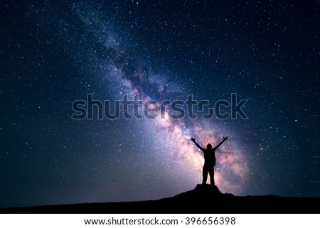 Landscape with colorful Milky Way. Night sky with stars and silhouette of a happy man with backpack and raised up arms on the stone. Space background - stock photo