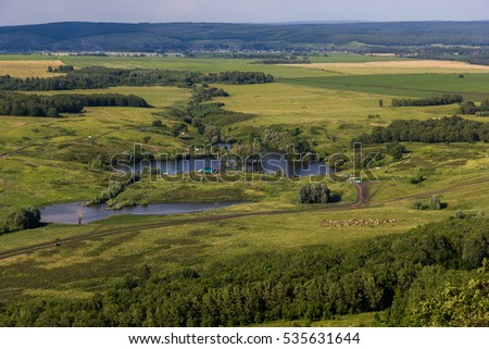 Landscape with cows, lake, forest. View from the mountain Toratau