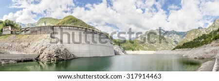 Landscape with dam for the production of electrical energy in the mountains