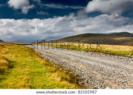 Landscape with dirt road in the mountains under cloudy sky