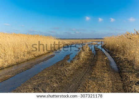 landscape with dirty road wit puddles in steppe - stock photo