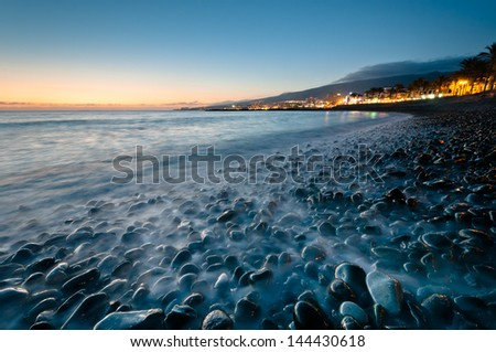 Landscape with flowing water on rocks at time of sunset - stock photo