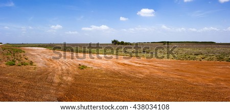 Landscape with gravel roads in the tropical summer Wet Season  at Roebuck Plains near Broome, North Western Australia, a region of natural grasslands  with fine alluvial and estuarine sediments  .