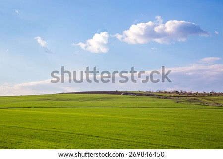 landscape with green field and blue sky with clouds - stock photo