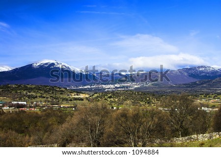 Landscape with green fields, a village, snow mountains and a blue sky