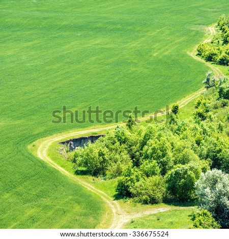 Landscape with green grass field with nearby forest and country road passing by. Aerial view - stock photo