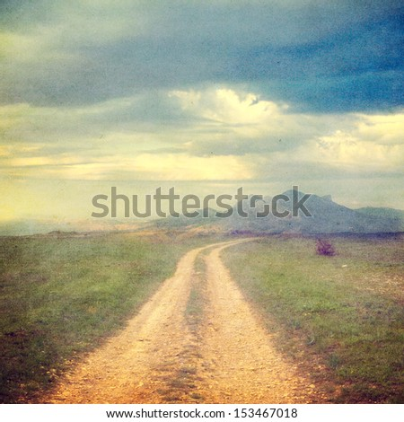 landscape with green grass, road and clouds-picture in retro style - stock photo