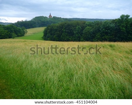 landscape with green meadow and a church on a hill in distance