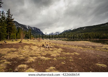 Landscape with high mountain lake with huge Rocky Mountains in the background. - stock photo
