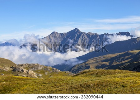 Landscape with high mountain peaks above the clouds located in National Park of Mercantour in Southern France. The view is from Cime de la Bonette which is the highest European asphalted road at 2860m - stock photo