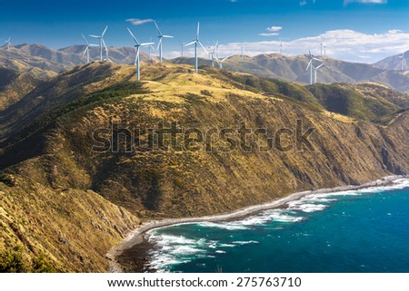landscape with hills, ocean and wind turbines - stock photo