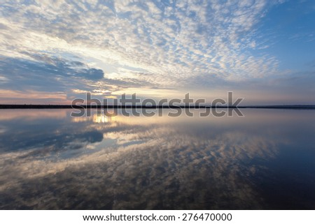 Landscape with lake reflection clouds. Beautiful summer sunset at the river - stock photo
