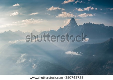 Landscape with majestic mountains in the blue haze and a beautiful sky with clouds - stock photo