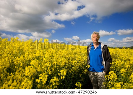 Landscape with man in yellow cole seed and clouds