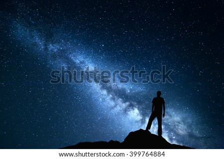 Landscape with Milky Way. Blue night sky with stars and silhouette of a happy man on the stone. Beautiful Universe. Space background - stock photo