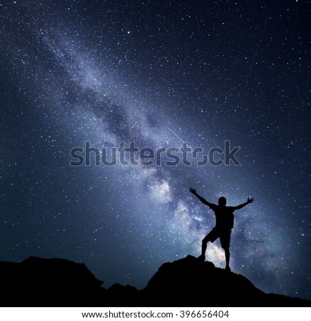 Landscape with Milky Way. Night sky with stars and silhouette of a happy climber with backpack and raised up arms on the mountain. Space background - stock photo