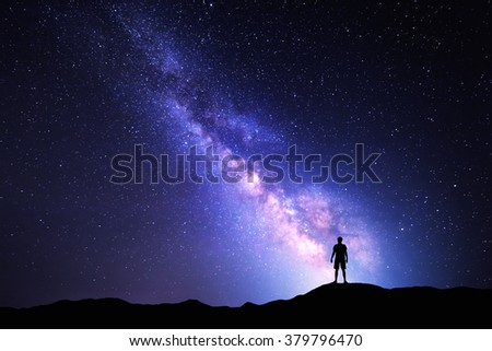 Landscape with Milky Way. Night sky with stars and silhouette of a standing happy man on the mountain. - stock photo