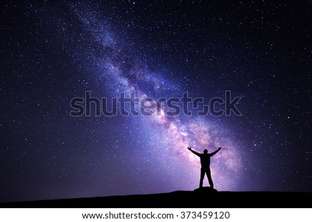 Landscape with Milky Way. Night sky with stars and silhouette of a standing man with raised-up arms - stock photo