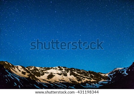 Landscape with mountain peaks and stars at midnight - stock photo