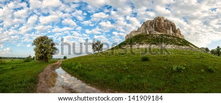 Landscape with mountain, road and clouds reflection in puddle - stock photo