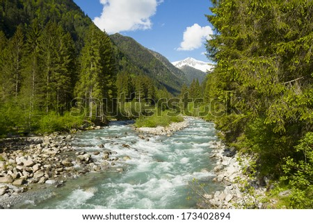 Landscape with mountains trees and a river in front - stock photo