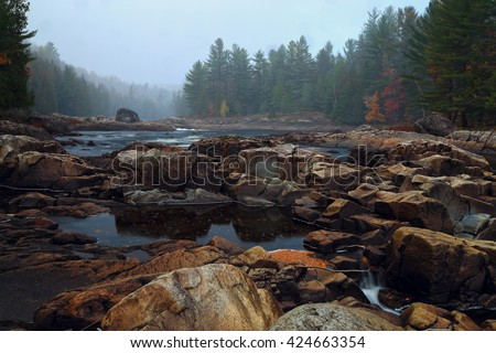 Landscape with mountains trees and a river in front.  Mountain river in fall forest with red yellow leafs and rocky shore. River in Quebec. Mountain river in autumn time. Stone River, Riverside rocks  - stock photo
