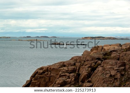 Landscape with ocean and red granite boulders and a sailing boat at the Swedish west coast.