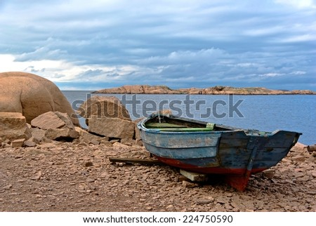 Landscape with ocean and red granite boulders and an old rowing boat.