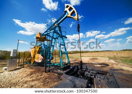 Landscape with oil pump under blue sky with clouds in a sunny day - stock photo