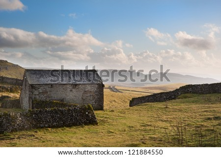 Landscape with old stone barn and flint stone walls on beautiful Autumn sunset evening