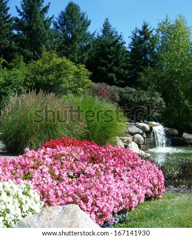 Landscape with pink flower beds tall decorative grass and waterfall