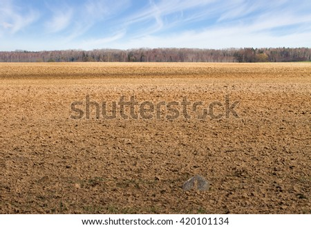 Landscape with plowed field in early spring.