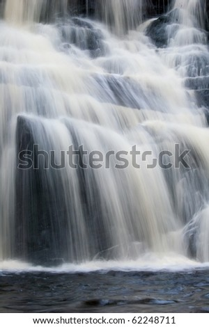 landscape with powerful falls on the mountain river