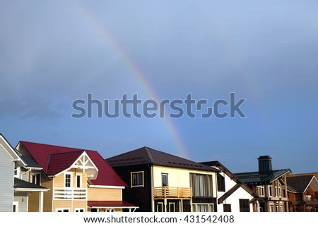 Landscape with rainbow after rain above modern cottage village homes in summer day horizontal photo