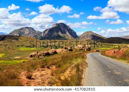 Landscape with road and rock formation in central Madagascar on a sunny day - stock photo