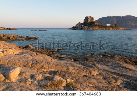 Landscape with rocky coastline and islet at sunset in Kos island, Greece - stock photo