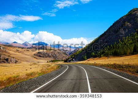 Landscape with rural asphalt road through the prairie and the mountains. Summer day. Steppe landscape. Summer steppe. Beautiful landscape. Summer landscape. Steppe. Road. Mountains. Adventure