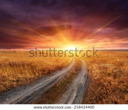 Landscape with rut road in steppe to sunset - stock photo