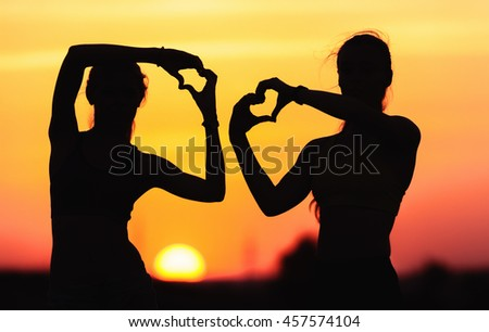 Landscape with silhouette of young sporty women holding hands in heart shape on the background of colorful sky at sunset in summer time. Happy girls