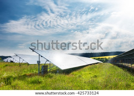 Landscape with solar power plant. Solar panels in sunny summer countryside under sun rays and blue sky. Solar power generation. Czech Republic, Europe - stock photo