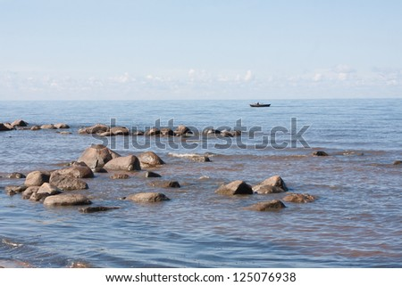 Landscape with stones in the sea and the boat
