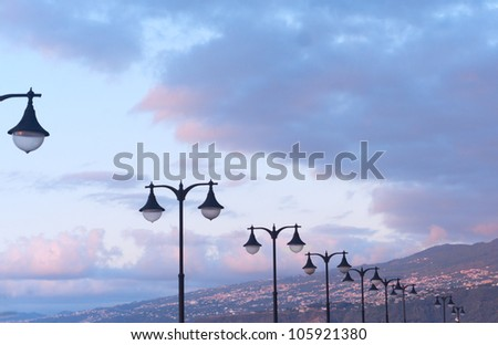 Landscape with street lamps against sunset sky - stock photo
