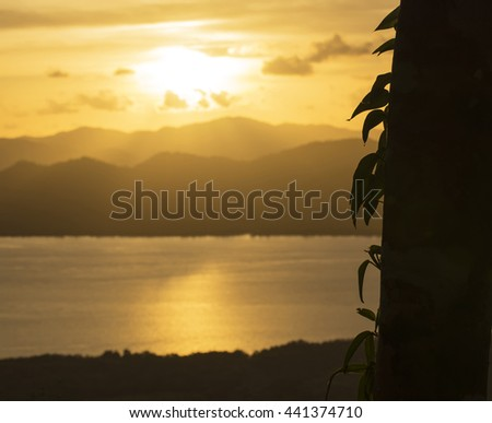 Landscape with sunset at the seashore over mountain range