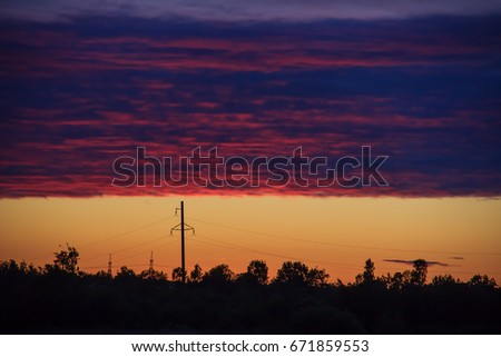 Landscape with sunset on the background of the forest and electrical towers