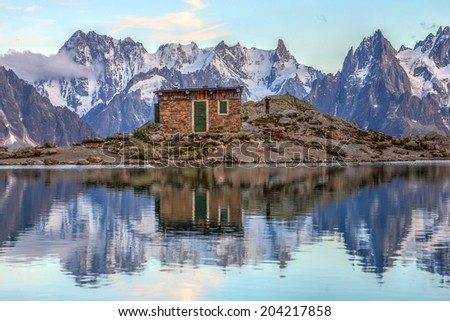 Landscape with the ancient shelter from Lac Blanc in front of a majestic backdrop of the Grandes Jorasses peaks of the Mont Blanc Massif, European Alps, France during sunset. - stock photo