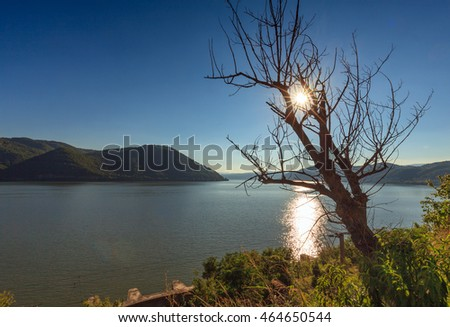 Landscape with the Danube river and surrounding limestone mountains in Romania
