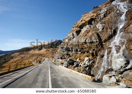 Landscape with Transfagarasan, a famous road in Romania, crossing the mountains, near a small waterfall - stock photo